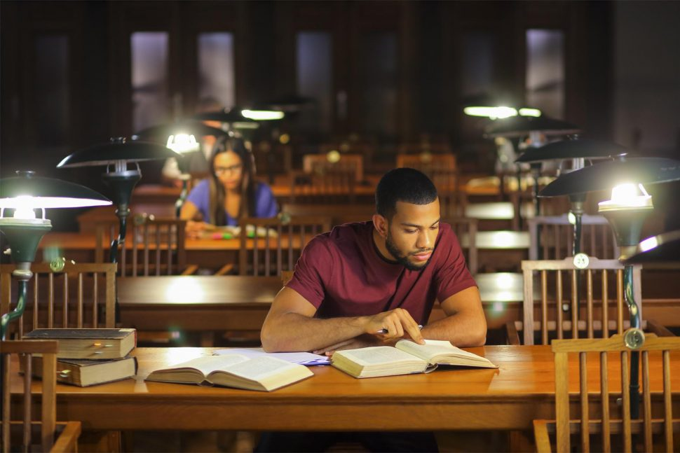 Young afro-american man studying in the library