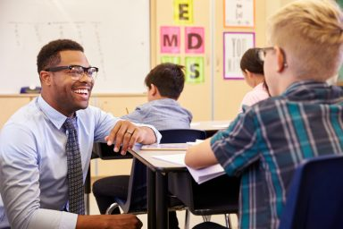 African American Male teacher assisting a student in class