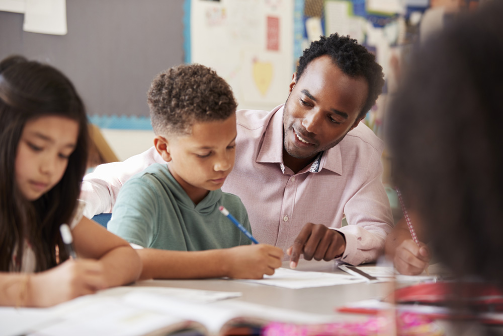 Male African American Teacher helping young student