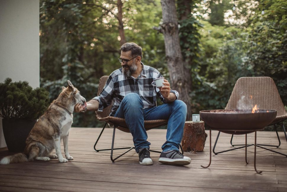 male teacher drinking coffee with a dog on a porch