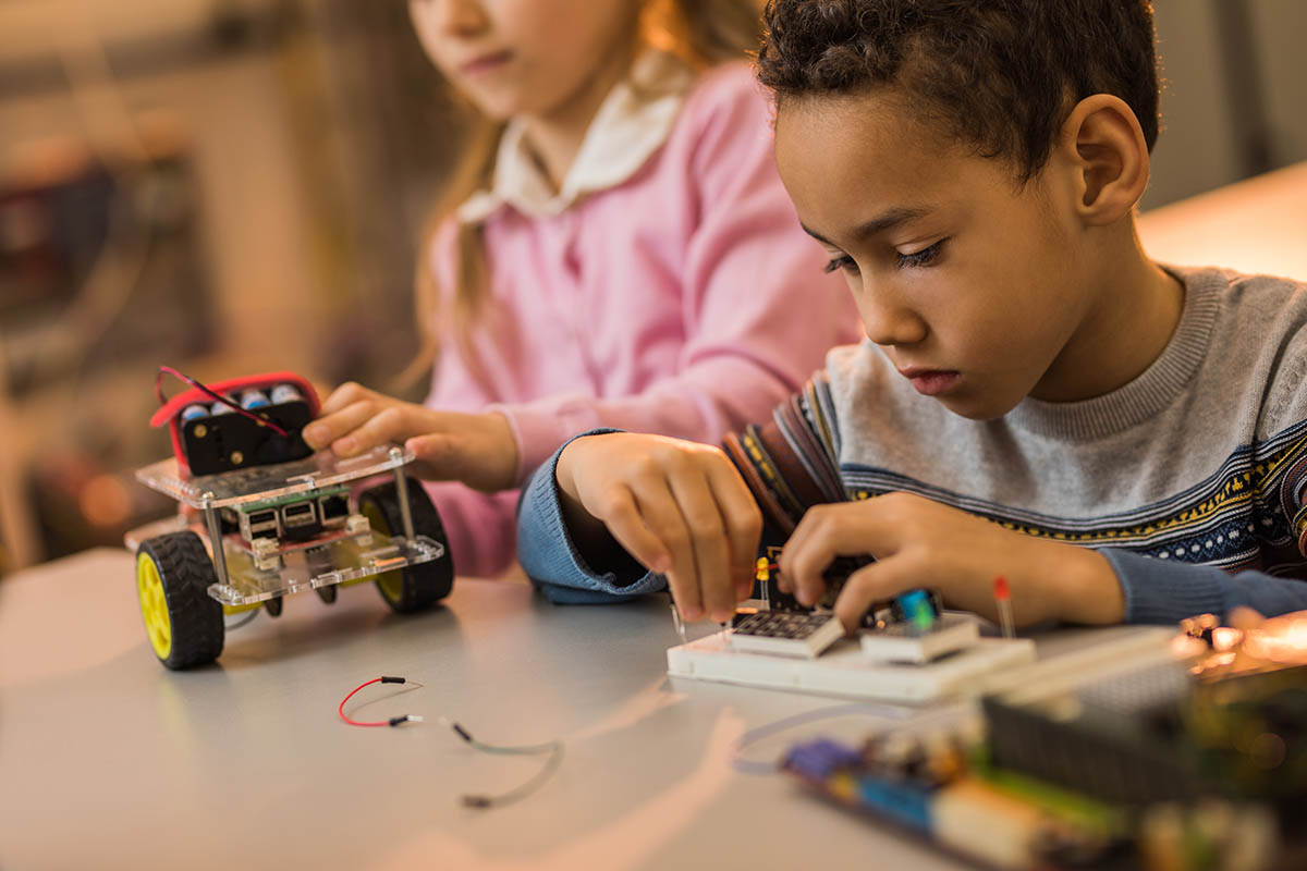 Small African American engineer making robotic parts while working with his friend in laboratory.