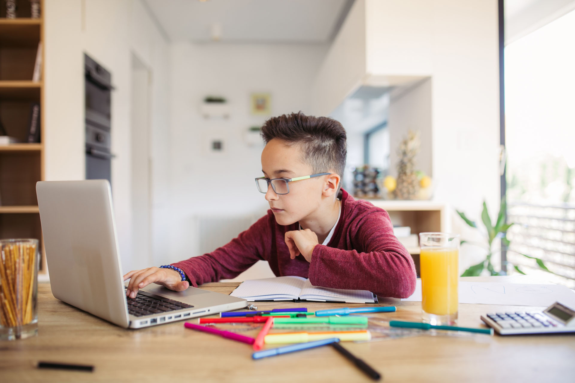 Student working on a laptop and taking classes online at home