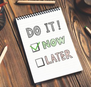 Do it Now, not later written on a tablet with a check mark on the now