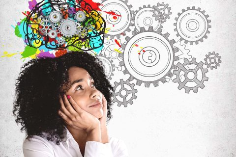 Girl thinking about cognitive dissonance Smiling young African American woman in white shirt looking at colorful brain sketch with gears drawn on concrete wall. Concept of brainstorming