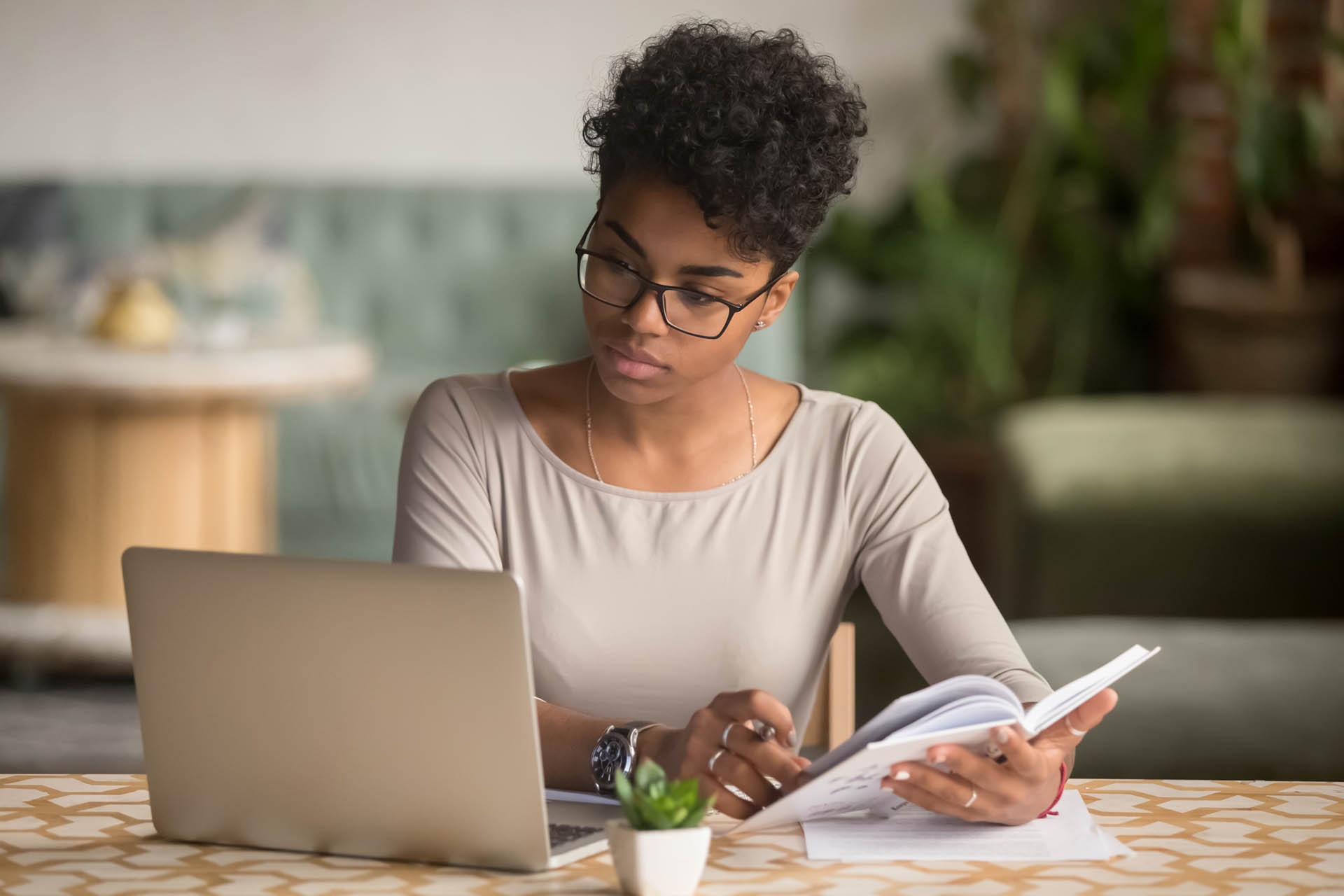 Focused young african american businesswoman or student looking at laptop holding book learning, serious black woman working or studying with computer doing research or preparing for exam online