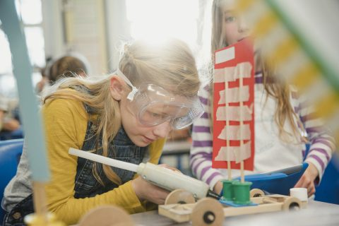 Elementary school children work together to build 3d models using recycled materials during class. This is a school in Hexham, Northumberland in north eastern England.