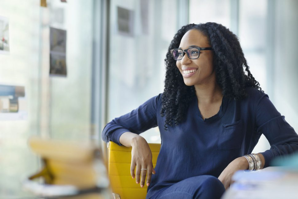 Portrait of young Black female woman designer owner entrepreneur small business new hire intern smiling proud dedicated passionate looking at camera sitting at desk in creative design studio office startup company contemporary modern daylight bright sunny natural light curly hair eyeglasses
