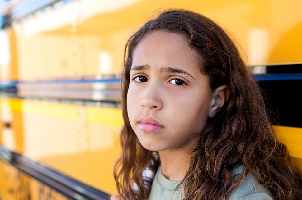 sad girl next to a school bus
