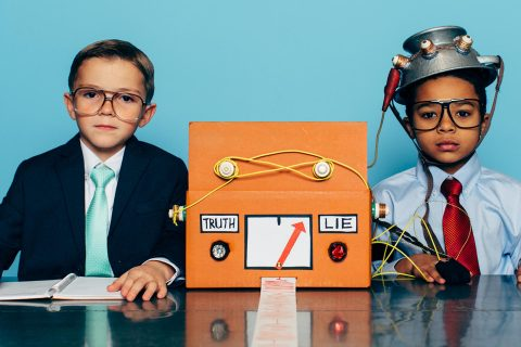 Two young boys and businessmen dressed in suits and glasses sit at a desk with a homemade lie detector machine. This serious interview is conducted in an office and the machine is predicting a lie from the job candidate. Dishonesty will eventually catch up to you.