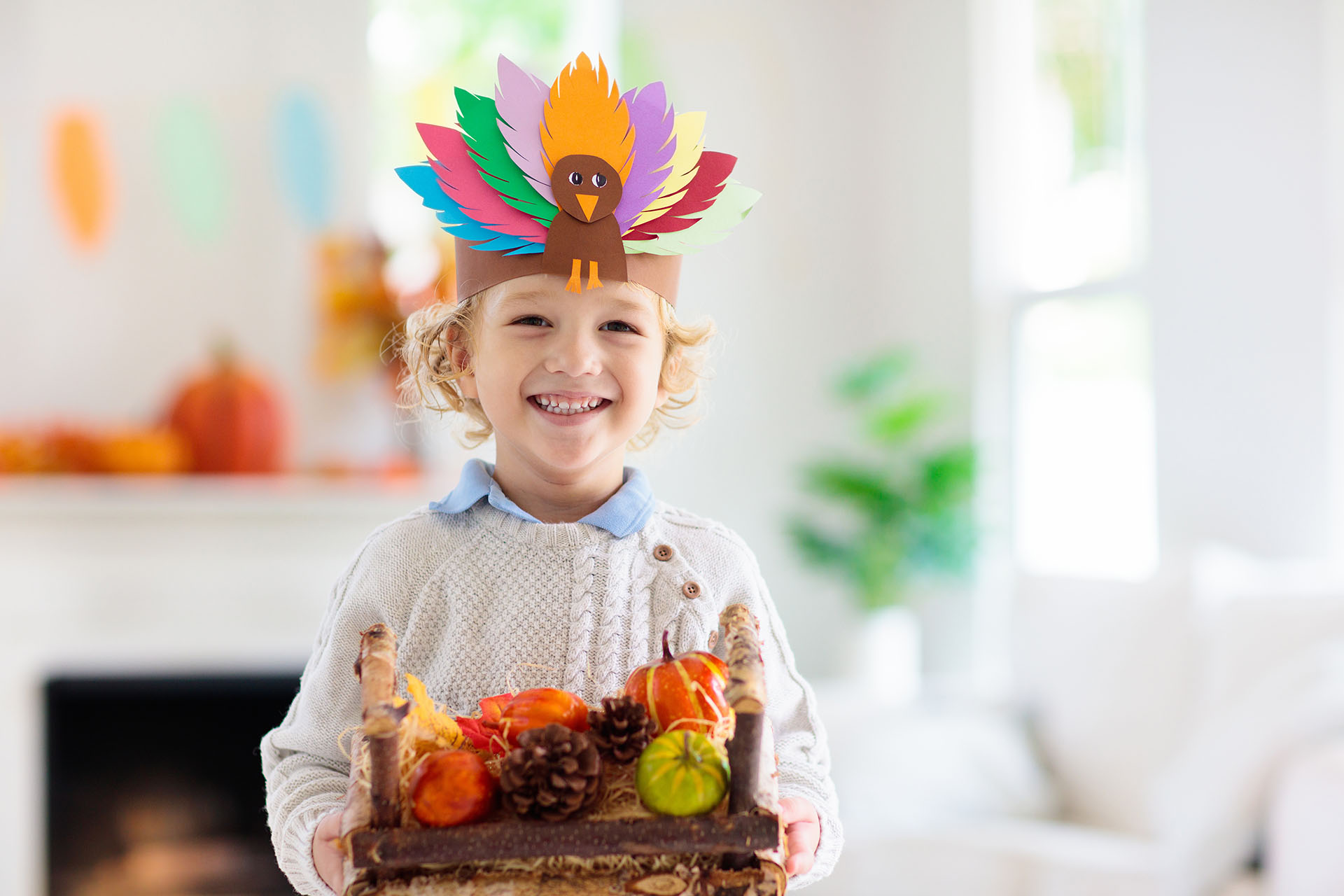 Child celebrating Thanksgiving. Kid holding pumpkin in paper turkey hat. Autumn fun crafts and art. Little blond curly boy in decorated living room. Warm knitted wear. Fall season decoration.
