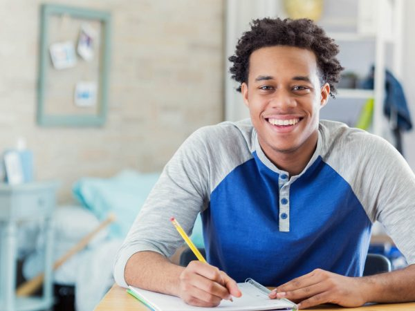 Cheerful African American teenage boy studies in his room. He is smiling at the camera. He is writing in a spiral notebook.