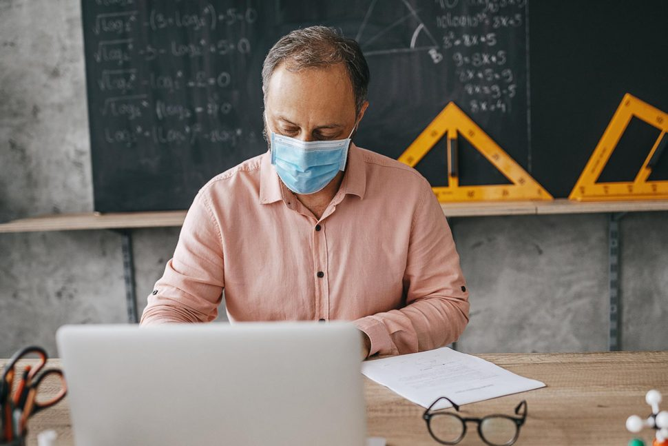 High school professor in classroom using laptop and wearing n95 face mask