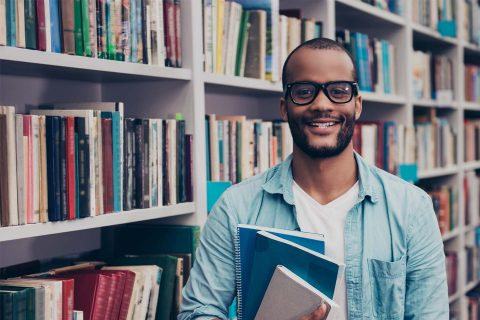 Young cheerful attractive successful african nerdy student is standing with books in the school library archive room, many tomes of ancient textbooks on shelves on the background behind