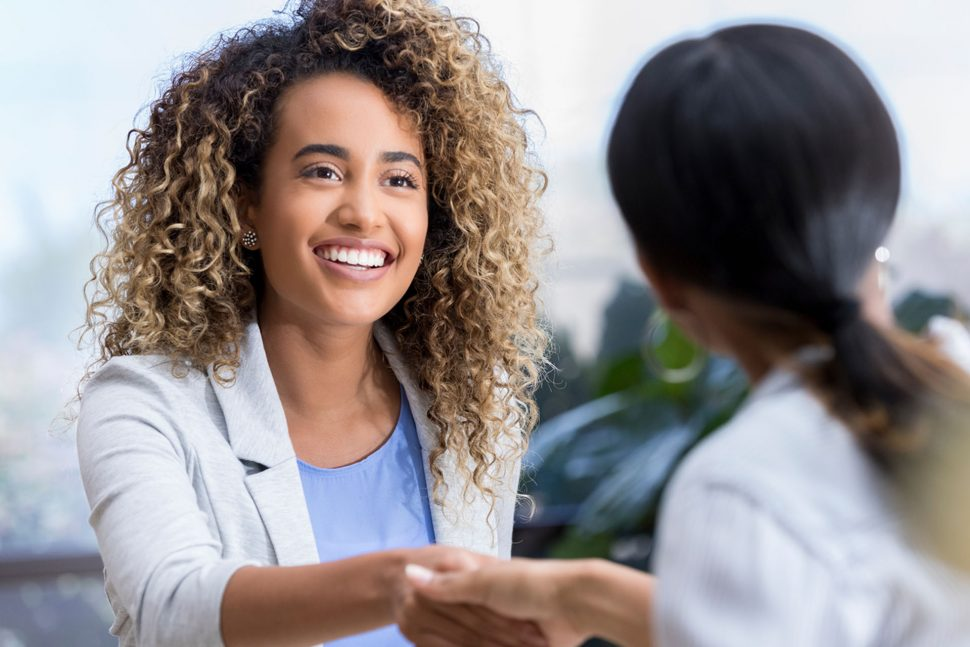 Attractive young mixed race businesswoman shakes hands with a female colleague during a teacher interview at a job fair.
