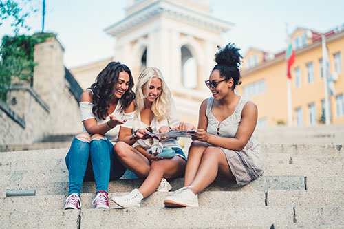 Three girls sitting on the stairs and using paper map for navigation