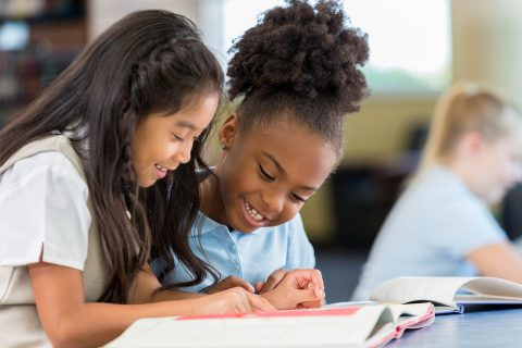 Happy female elementary age students in school uniforms are sitting at a desk in the school library and reading a book together. A Filipino elementary age girl sits with an African American classmate and reads a book together in the school library.